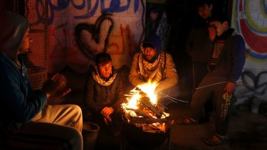 Palestinians, who get only several hours of electricity a day, sit around a fire outside their home in Gaza City.