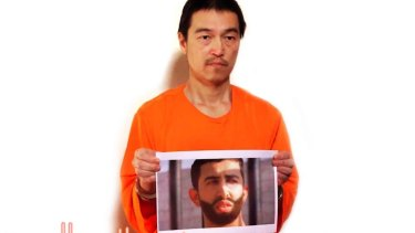 This image from a YouTube video posted by jihadists purports to show Kenji Goto holding a photo of Jordanian pilot Muath al-Kasaesbeh.
