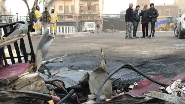 People inspect the aftermath of a car bomb in Baghdad on December 4.