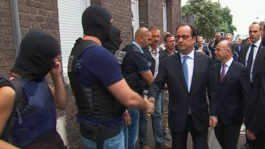 French President Francois Hollande shakes hands with police and security personnel in Normandy.
