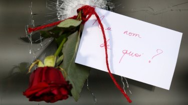 """A rose in a bullet hole with a note that translates to """"In the name of what?"""" at La Belle Equipe cafe."""