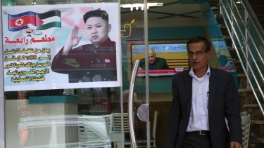 A Palestinian customer walks out of a shawarma restaurant with a poster of North Korean leader Jim Jong at the entrance of it in Jebaliya refugee camp, Gaza Strip.