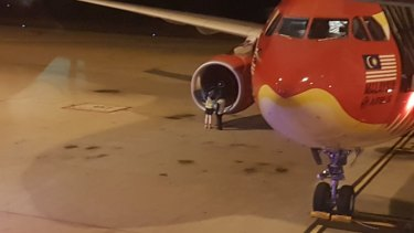 Groundstaff next to the engine of Air Asia X flight D7207 after it was diverted to Brisbane Airport.
