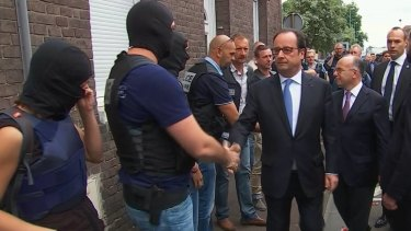 French President Francois Hollande shakes hands with police and security personnel in Normandy, France.