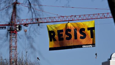 The banner with activists dangling from the side.