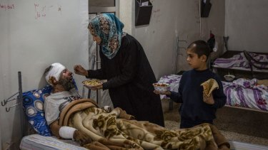Kawther al-Obaid feeds her husband, who was wounded in an air strike on Raqqa, as their son Bassam looks on at a hospital in Tal Abyad, Syria.