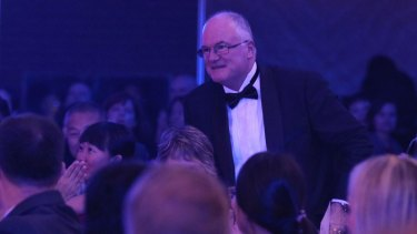 Professor Craig Anderson, a founder and principal director of The George Institute for Global Health, walks up to receive the social responsibility award.