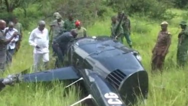 In an image taken from local television footage, Jumanne Maghembe, Tanzania's Minister for Tourism and Natural Resources, and officials walking towards helicopter wreckage at the site where a British pilot was killed after his helicopter was fired on by elephant poachers in Tanzania last month.