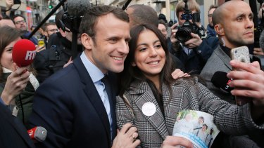 Independent centrist presidential candidate Emmanuel Macron poses for a selfie after visiting a police station in Paris.
