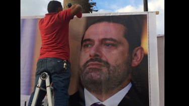 """Workers hang a poster of former PM Saad Hariri in Beirut saying: """"We are all Saad""""."""