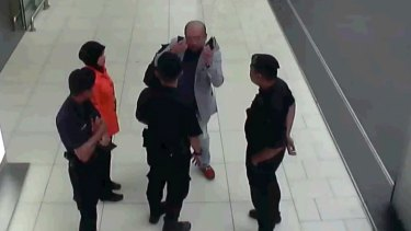 In this image made from security camera footage and provided by Fuji Television, Kim Jong-nam gestures towards his face while talking to airport security at Kuala Lumpur International Airport.