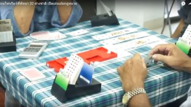 Bridge players keep playing as authorities raid a Jomtien and Pattaya Bridge Club meeting in Pattaya.