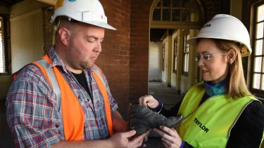 Archaeologist David Marcus and NSW Attorney-General Gabrielle Upton examine the boot at the old Children's Court.