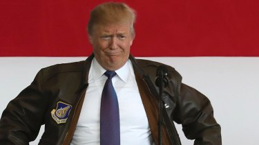 US President Donald Trump puts on a military jacket as he meets the US troops at the US Yokota Air Base, as part of his Asian tour.