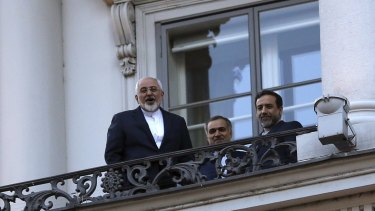 Iranian Foreign Minister Mohammad Javad Zarif, left, talks to journalists from a balcony of the Palais Coburg hotel in Vienna.