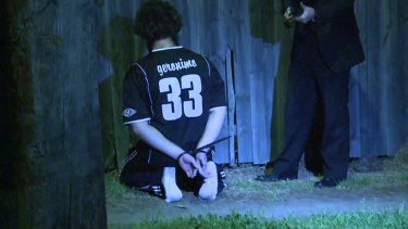 A man detained by police during a raid kneels on the ground in Sydney.