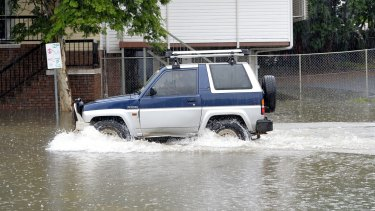 A car driving through flood waters in Brisbane last year