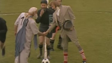 Players shake hands at the start of the match in the sketch.