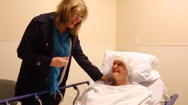 Kate (formerly Bill) Rohr talks with her doctor Marci Bowers (left) after surgery.