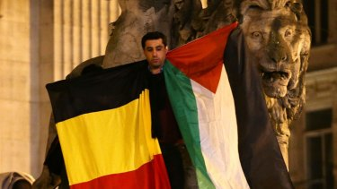 A man waves a Belgian and Palestinian flag as a mark of solidarity at the Place de la Bourse on Tuesday.