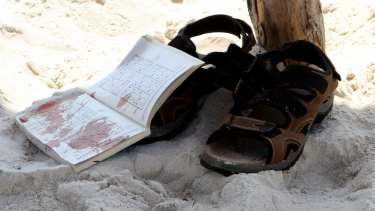 The bloodstained belongings of a tourist on the sand.