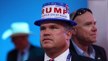 A delegate wears a hat with a campaign sticker for Donald Trump.