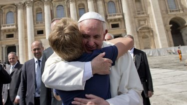 Pope Francis hugs a young boy at the end of his weekly general audience in St Peter's Square on Wednesday.