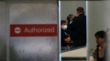 Masked customs officers monitor a screening area for international passengers at Newark airport, New Jersey.