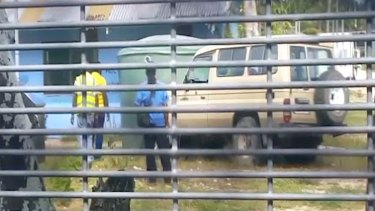 Video footage appears to show authorities using a 4WD to ram rainwater tanks at the centre.