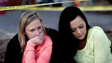 Churchgoers were left reeling from the shooting. Amanda Padula, left, and Deborah Young sit outside Altar Church in Coeur d'Alene, where pastor Tim Remington was shot.