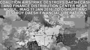 This image made from a video released by the US military shows an air strike targeting an Islamic State group cash and finance distribution centre near Mosul, Iraq.