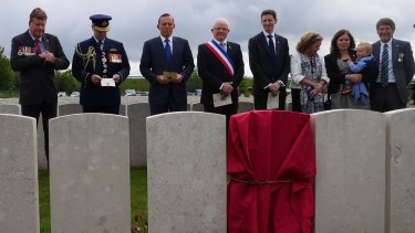 Tony Abbott and the official party, including members of the Kirkland family, before the new headstone of Corporal Athol Kirkland.