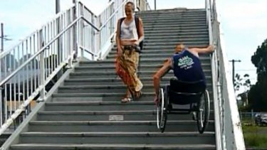 A wheelchair-bound man struggles down the stairs in the video.
