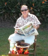 The conman seen reading the Fiji Sunday Times newspaper with what he claims is a bowl of kava.