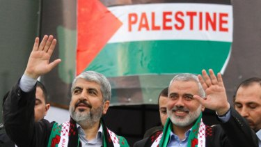 Hamas chief Khaled Meshaal, left, and then Hamas leader in Gaza Ismail Haniyeh wave to Palestinian Hamas supporters at the 25th anniversary of the militant group  in Gaza in 2012.