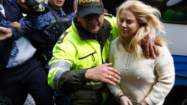 A Colombian police officer escorts Cassandra Sainsbury into court in August.