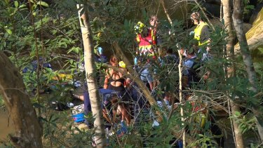 Emergency service workers try to save the life of a man who fell at Somersby Falls.