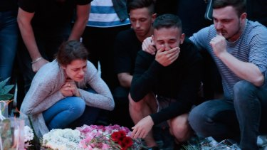 People mourn near the crime scene at OEZ shopping centre the day after a shooting spree left nine victims dead.