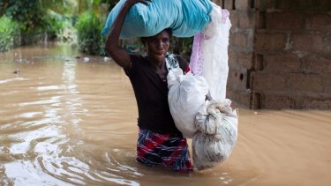 Assilia Joseph carries her belongings through flood waters in Haiti.