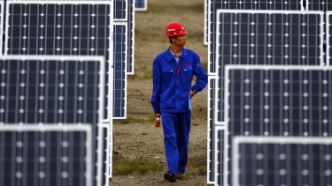 A worker inspects solar panels at a solar farm in Dunhuang, China.