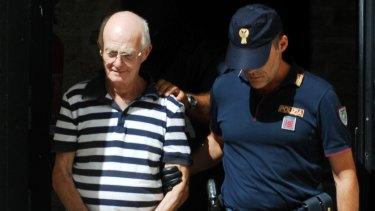 An Italian police officer takes in custody Ugo Di Leonardo,another of the 11 men suspected of helping Denaro.