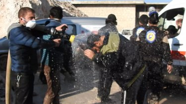 Civil defence workers spray water on victims after the chemical weapons attack near Idlib.
