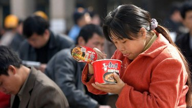 A woman eating instant noodles at Beijing Railway Station. The industry grew in parallel with an economic boom that was fuelled by the migration of low-cost workers from the countryside.