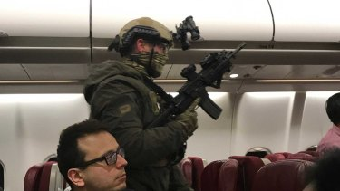 Police storm flight MH128 after a man allegedly tried to enter the cockpit.
