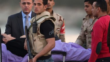 Hosni Mubarak is escorted on a bed into an ambulance prior to appearing in court on Thursday.
