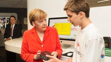 Michael Schultz shows his tricoder to German Chancellor Angela Merkel.