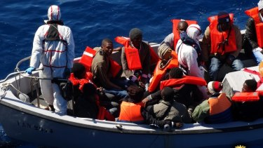 Rescued migrants wear life-jackets as they sit in an Italian navy's boat in the Sicilian Channel, Mediterranean Sea, on Friday.
