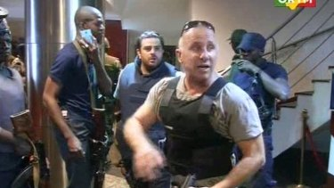 In this TV image taken from Mali TV ORTM, a security officer gives instructions to other security forces before moving against Islamist gunmen inside the Radisson Blu Hotel in Bamako, Mali.
