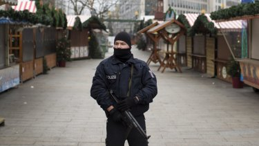 An armed police officer stands guard as the festive stalls remain closed at Berlin Christmas market in Berlin, Germany after a terror attack.