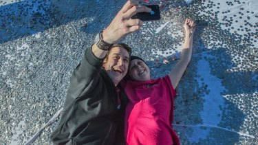 Connie and Samuel Johnson luxuriate in a sea of 5c coins for the Love Your Sister big heart project in May.